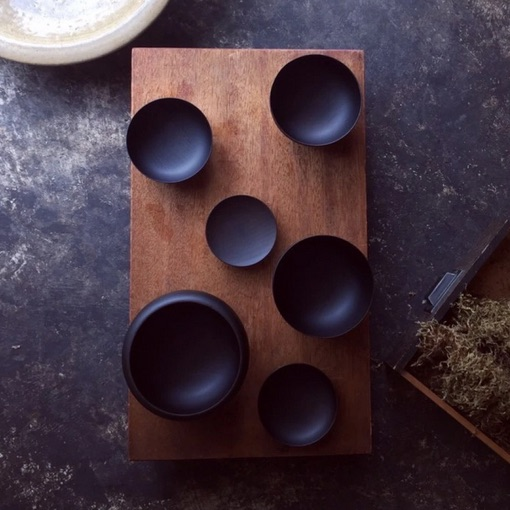 A set of six black Japanese bowls of different sizes, laid out on a table.