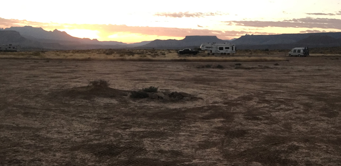 The sun, rising over some mesas and rock formations.