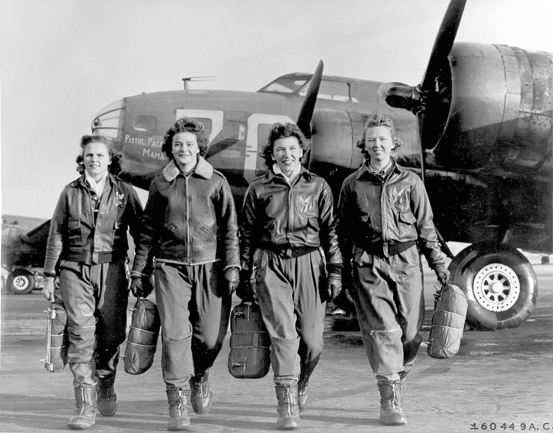 A black-and-white image of four World War 2-era women on a runway, walking away from a B-17 bomber.